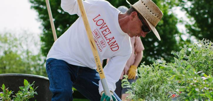 A volunteer uses a shovel to plant a tree at the Audubon Loveland Visitor Center.