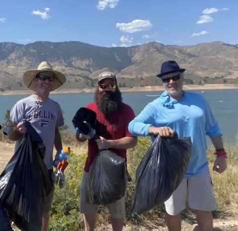 Tres personas de pie en el depósito Horsetooth sosteniendo bolsas de basura después de completar una limpieza de basura.