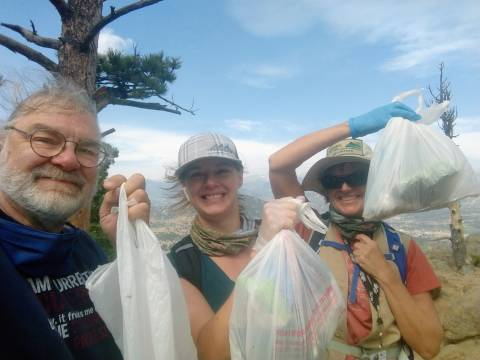 Three volunteers smiling at the camera and holding up the trash bags they filled while picking up litter at Hermit Park Open Space.