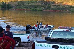 Larimer County Boat Patrol Ranger boat docked and viewed from shore with Ranger trucks.