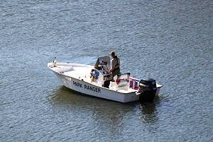 Larimer County Ranger patrolling a reservoir on a boat.