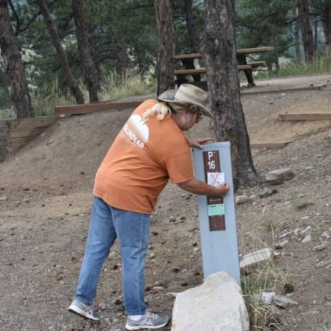 Anfitrión voluntario del campamento que verifica que la etiqueta de reserva del campamento tenga la fecha correcta.