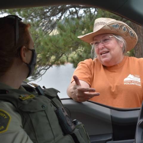 Anfitrión voluntario del campamento hablando con el guardaparques a través de la ventana del vehículo.