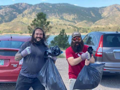 Two volunteers proudly displaying the trash bags they filled while picking up litter at Horsetooth Reservoir.
