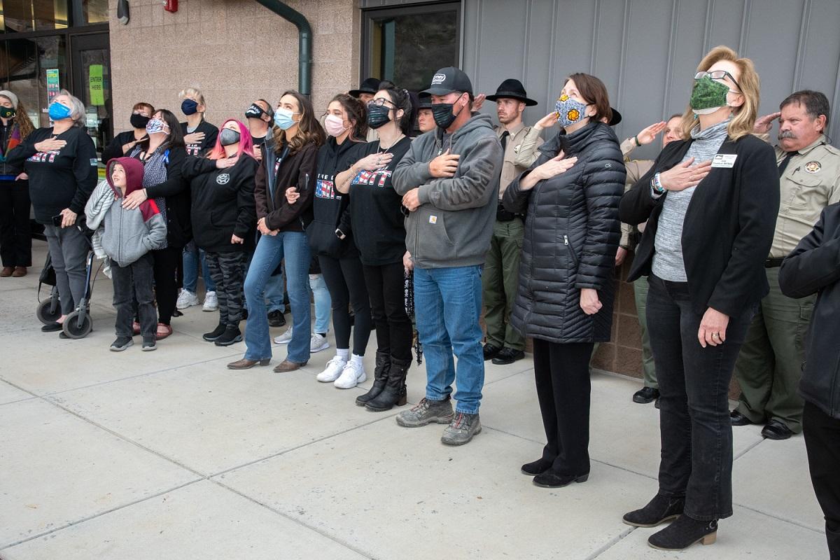 Imagen 3: Familia y personal observan juntos cómo se iza la bandera para la Dedicación Conmemorativa, cortesía de Charlie Johnson